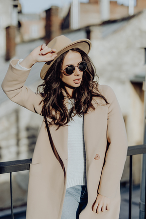 Outdoor portrait of young beautiful fashionable woman posing in street. Model wearing stylish gray coat, hat, white round sunglasses. Female fashion concept, city lifestyle Stock Photo - 124465102