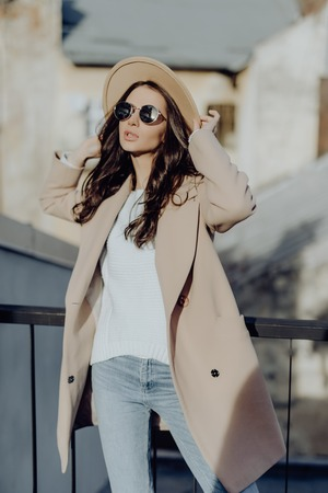 Outdoor portrait of young beautiful fashionable woman posing in street. Model wearing stylish gray coat, hat, white round sunglasses. Female fashion concept, city lifestyle