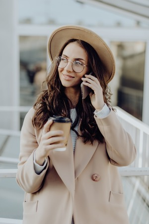 Attractive and stylish woman in eyeglasses talking on smart phone and holding paper cup of coffee in hand while standing outdoors. Trendy hipster girl in gray coat using mobile phone to have a talk