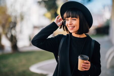 Beautiful young woman holding coffee cup and smiling while walking along the street