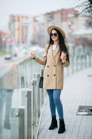 Pretty woman in coat drinking coffee outside in the street Stock fotó