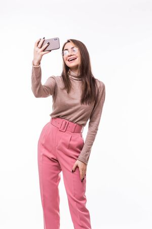 Portrait of a smiling cute woman making selfie photo on smartphone isolated on a white background