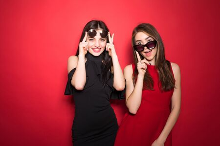 Photo of two posh women 20s in trendy outfit and sunglasses smiling at camera isolated over red background Banco de Imagens - 126566386