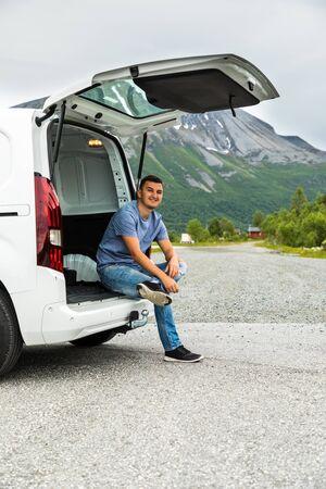 Le jeune homme conduisant la voiture dans les montagnes se détend au bord de la route