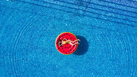 Aerial drone top photo of unidentified woman wearing a hat sitting in inflatable watermelon in tropical paradise beach resembling a pool