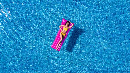 Slim young woman lying on air mattress in the pool Stockfoto - 127953495