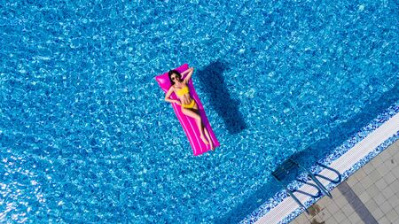 Slim young woman lying on air mattress in the pool Stockfoto - 127953500