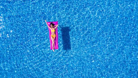 Sexy woman rest and sunbath on a float in the pool, top view aerial shot. Young woman in a bikini swimsuit floating on an inflatable pink mattress top view Stockfoto