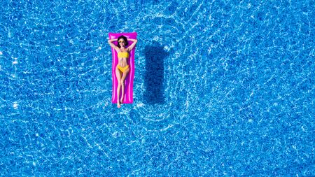 Slim young woman lying on air mattress in the pool Stockfoto - 127953511