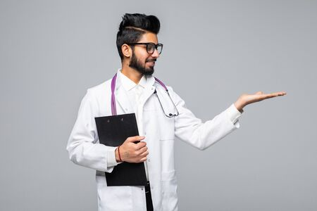 Handsome Indian Male Doctor presenting something. standing isolated over blue background