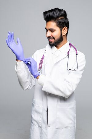 Indian male medic arranging blue latex gloves on hand isolated on white studio background 写真素材 - 129643613