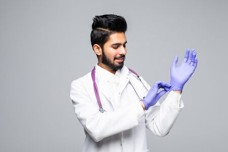 Indian male medic arranging blue latex gloves on hand isolated on white studio background 写真素材