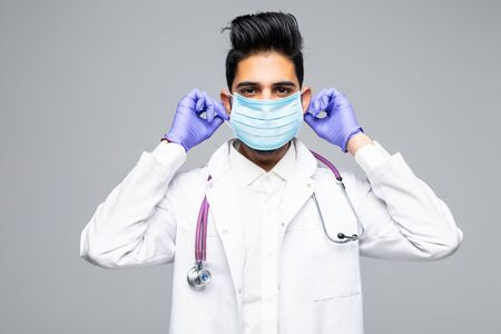 Portrait of a handsome beard doctor in scrubs with stethoscope and mask standing confidently , isolated on white background