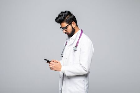 Side-view of indian male doctor looking at smartphone screen and sending text messages isolated on white background