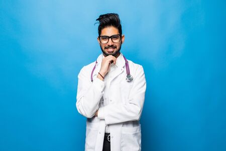 Portrait of doctor smiling isolated on blue background Imagens