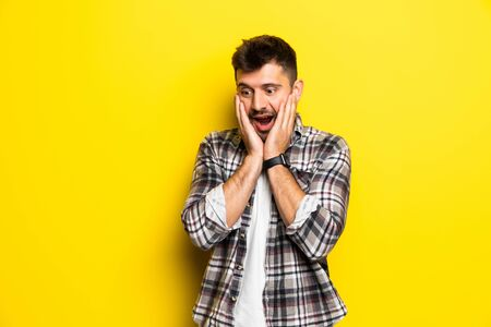 Portrait of scared man in panic nervous excited dressed in denim shirt keeps palm on face, feals fear, isolated on yellow background. Guy shocked by scene in front of him Foto de archivo