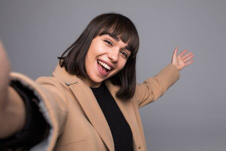 Cheerful woman wearing coat standing isolated over gray background, taking a selfie Stockfoto