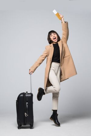 Happy young woman tourist jumping, holding suitcase and passport, flight tickets, isolated on white background