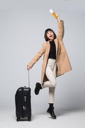 Turista joven feliz saltando, sosteniendo la maleta y el pasaporte, billetes de avión, aislado sobre fondo blanco.