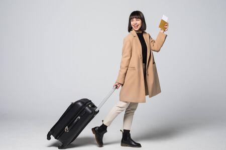 happy girl going on vacation with passport tickets and her suitcase over a white background