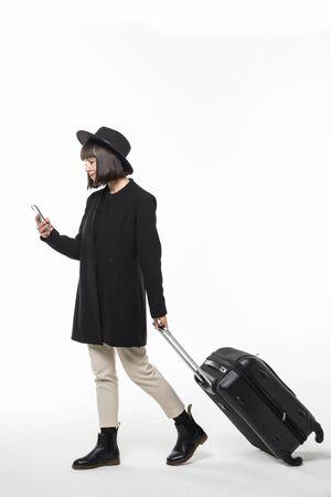 Ritratto laterale integrale della donna asiatica sorridente che cammina contro il fondo bianco isolato con la valigia ed il cellulare