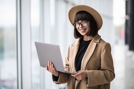 Portrait of woman working holding laptop standing against panoramic window with city view