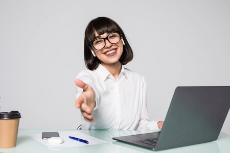 Lächelnde brünette Geschäftsfrau, die den Arm im hellen Büro ausstreckt Standard-Bild