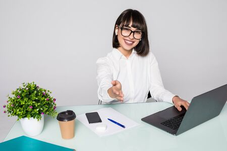 Smiling brunette businesswoman extending arm in bright office
