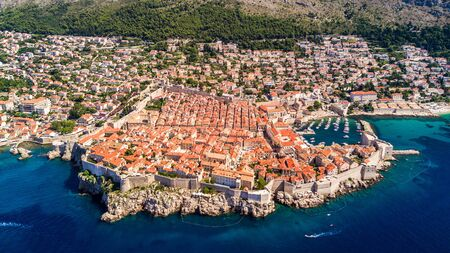 Dobrovnik, Croatia from above - Aerial drone footage of the historic city of Dubrovnik. City walls, blue sea and harbour.