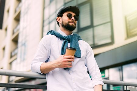 Enjoying fresh coffee. Handsome man in casual wear holding disposable cup and smiling while walking through the city street