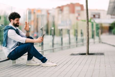 Handsome young stylish man talking in video chat via cell phone, sitting on the grass and speak with friends by video call