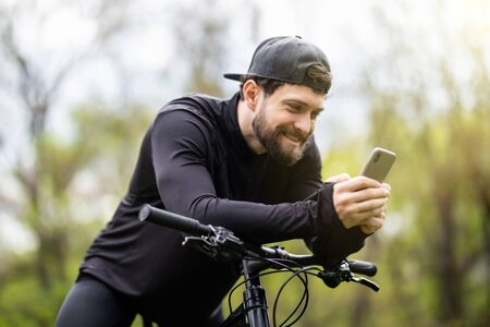 Happy bearded man cyclist rides in the sunny forest on a mountain bike.