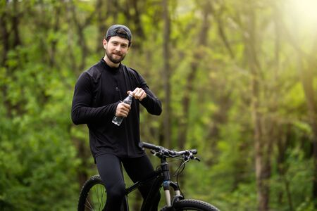Cyclist Resting and Drinking Water at Summer River Background. Healthy Lifestyle Concept. Stock fotó