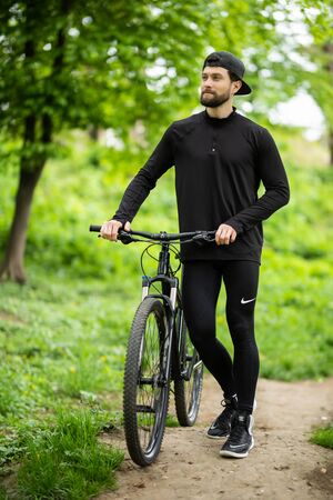 Professional cyclist carrying bicycle while riding off road in the forest Stock fotó