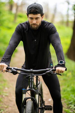 Feliz joven está montando bicicleta afuera.