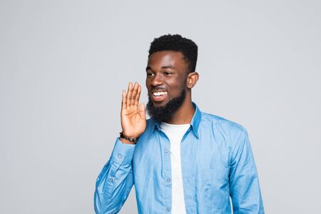 Portrait Of Young African Man Whispering Over White Background Stock Photo