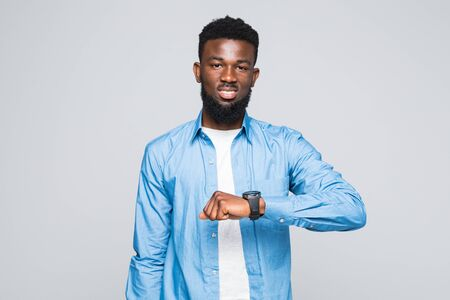 What time is it. Portrait of young attractive man with dark afro hairstyle in white t-shirt and red shirt pointing at hand watch with happy face expression, showing it time to eat.
