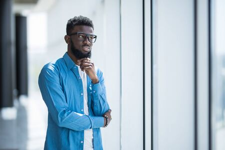 Young African designer looking through window thinking about the future 写真素材