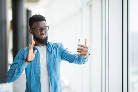Cheerful successful young African American manager with phone wave greetings on video call comunication 版權商用圖片