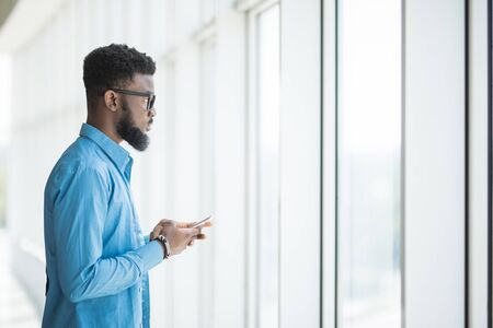 Young businessman using a mobile phone in the modern office space