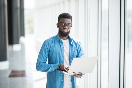 Love my job. Waist-up portrait of positive attractive african man in glasses is standing in office and holding modern laptop. He is looking at monitor with smile while typing on keyboard