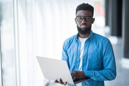 Excellent mood. Cheerful young african manager in glasses is working on laptop while sitting on table in modern office. He is looking at monitor with smile. Copy space in the left side