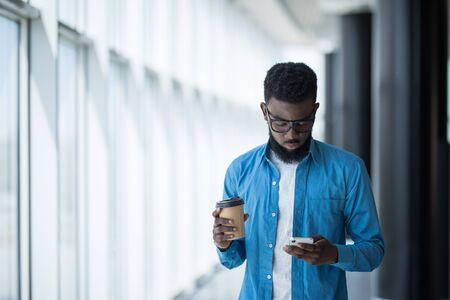 Young Afro American man standing in modern business building smiling and use phone
