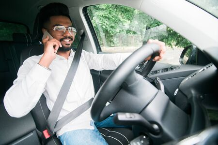 Closeup portrait, sad handsome young man in blue polo shirt sitting, driving in gray black sports car on cellphone with bad news, isolated outdoors background
