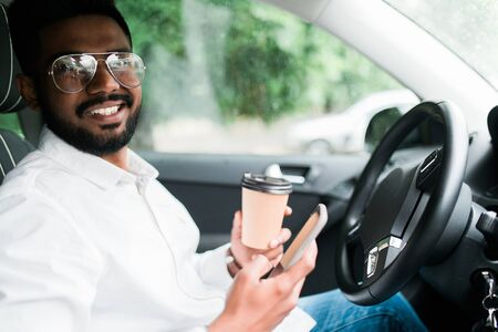 Stylish driver with a smartphone in hand and paper cup of hot coffee in the drivers seat. The concept of inattention at the wheel, rest, coffee break to cheer. Stock Photo