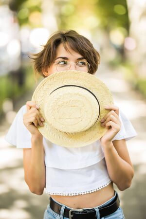 Young woman covering face with straw hat while walking in green park