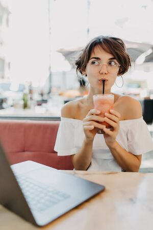 Young woman drinking smoothie while working on laptop in summer cafe Фото со стока