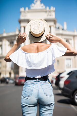 Rear view of woman walking on city street wearing hat enjoying happy pleasant moment of her vacations