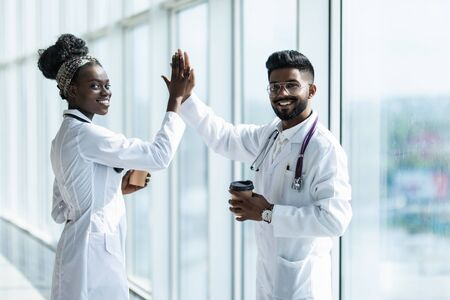 Full length shot of a indian male and african female doctor gesturing high-five isolated on white background