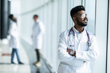 Portrait of a male Indian doctor standing in front of his colleague with a stethoscope around his neck